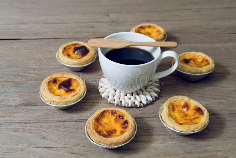 Coffee with egg tart in aluminum foil cup on wood table.  royalty free stock photo