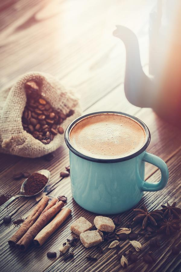 Coffee in enameled cup , sugar cubes, sack of coffee beans and spices. stock photo
