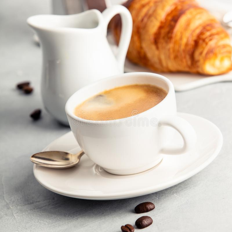 Coffee espresso in white cup with milk, jam and croissants. stock photo