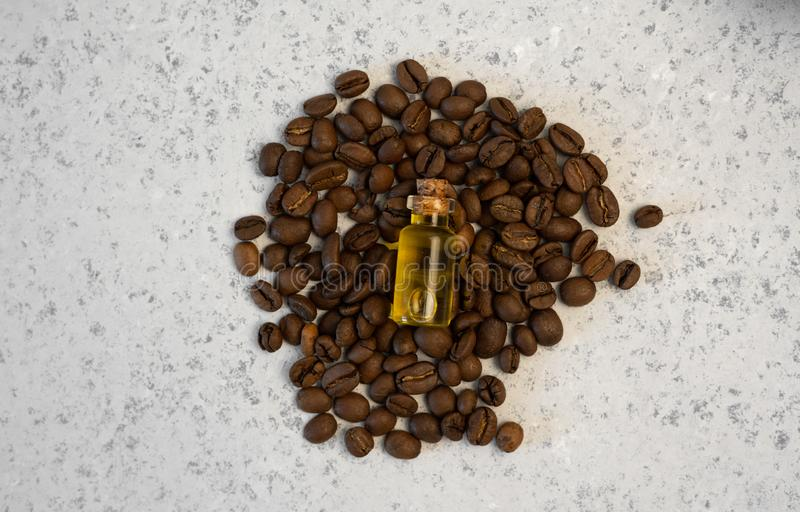 Coffee essential oil in a glass bottle, coffee beans on grey background royalty free stock photo