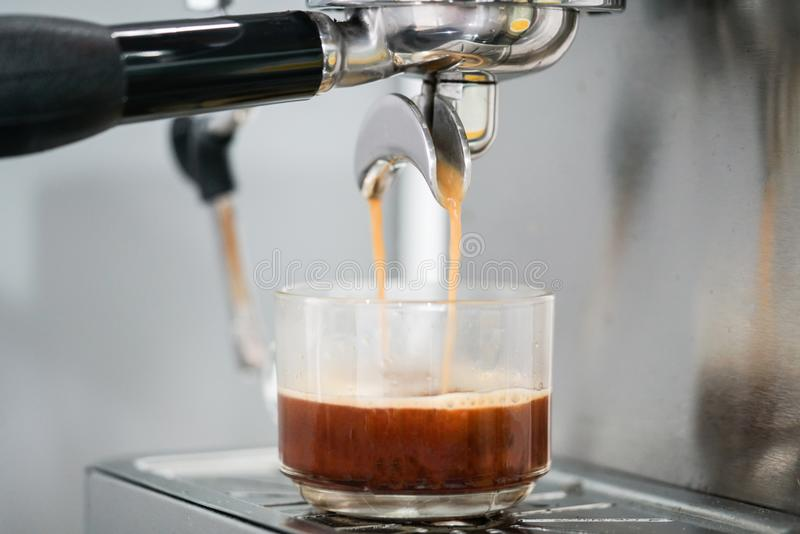 Coffee extraction from coffee machine in cup royalty free stock image