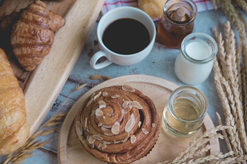Coffee and fresh breads served for breakfast on wooden trays stock image