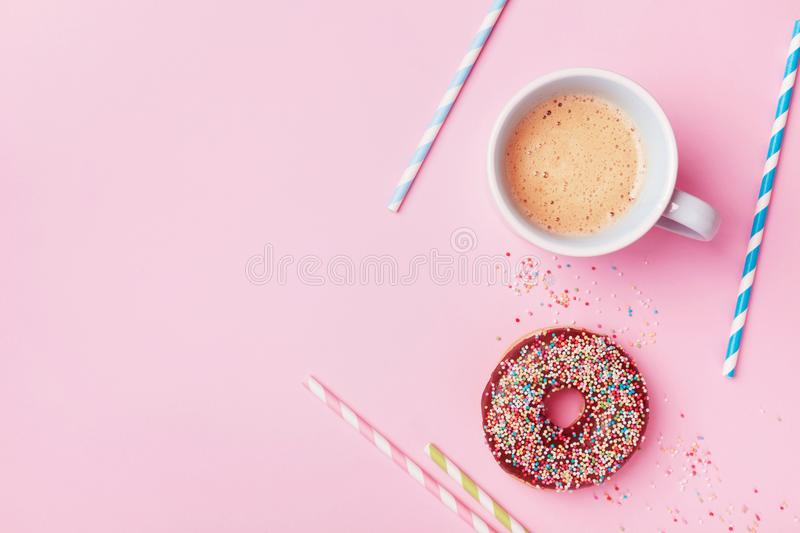 Coffee and fresh pastry of chocolate donut on pink pastel table top view. Flat lay. Cozy breakfast. stock photo