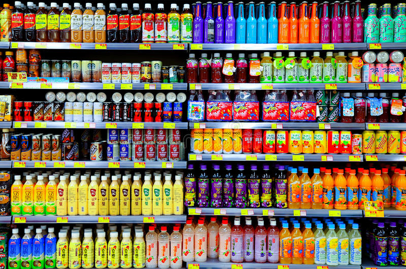 Coffee and fruit juices at supermarket. Assorted brands of coffee, fruit juices packed in bottles and cans on shelves at supermarket for sale