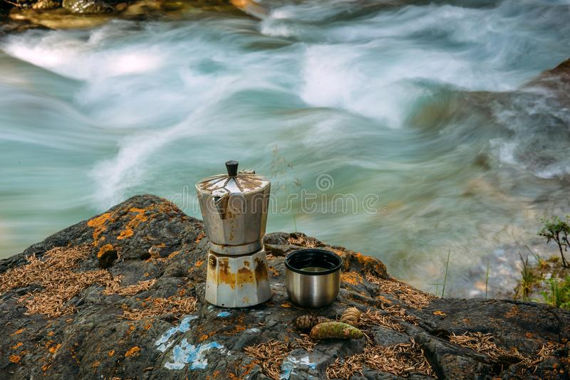 A coffee geyser and an iron mug stand on a large mossy stone near the fast mountain river. Tourist Parking or camping, coffee by. The river close-up, blurred royalty free stock images