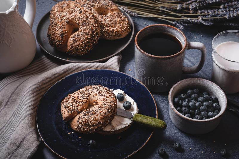 Coffee and gluten free seeded bagels with non dairy cream cheese and blueberries. stock images