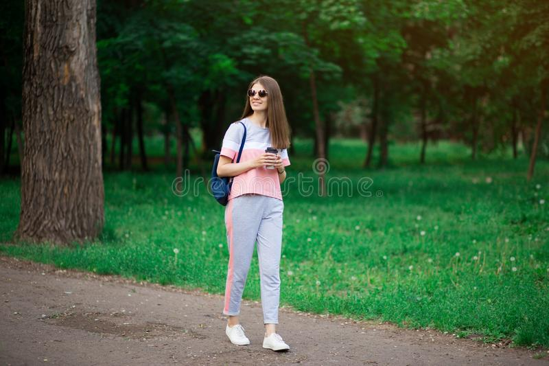 Coffee on go. Beautiful young woman in sunglasses holding coffee cup and smiling while walking royalty free stock image