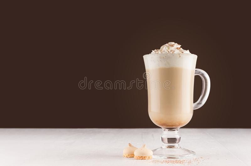 Coffee in goblet with chocolate powder, foam and biscuits in brown modern restaurant interior, copy space. Coffee  in goblet with chocolate powder, foam and royalty free stock images