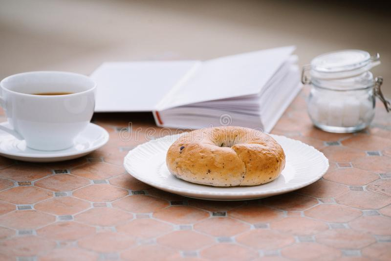 Coffee, a good book and bread for a good morning in cafeteria.  stock images