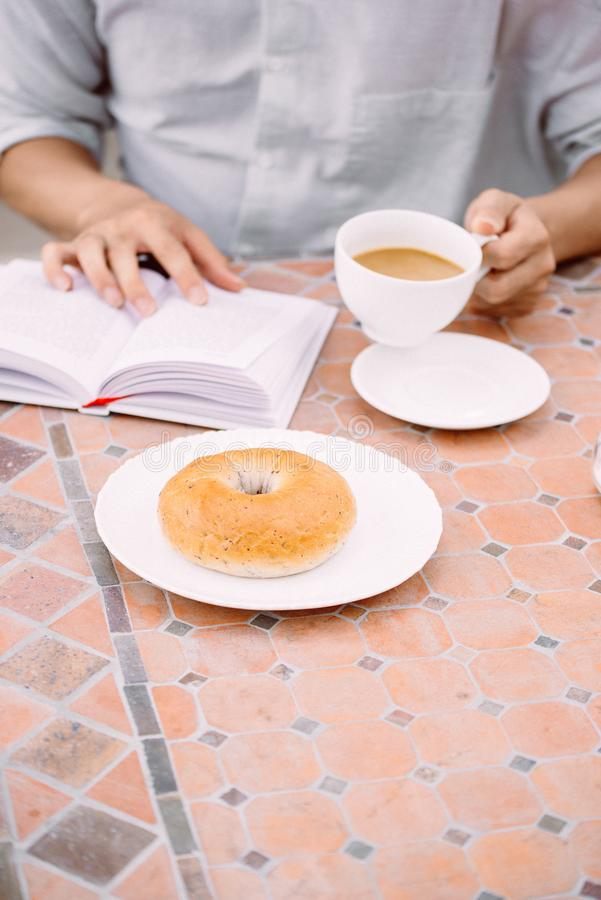 Coffee, a good book and bread for a good morning in cafeteria.  stock photo