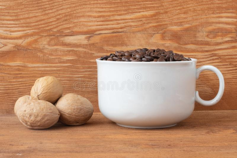 coffee grains in a cup with walnuts on a wooden background royalty free stock image