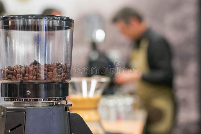 Coffee grinder with blurred barman in the background royalty free stock image