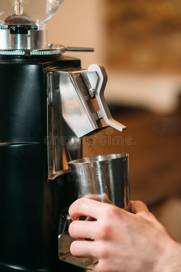 Coffee grinder fills drink in a cup. royalty free stock images