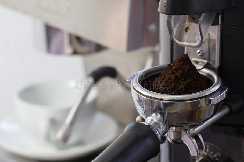 Coffee grinder grinding freshly roasted coffee beans stock photo