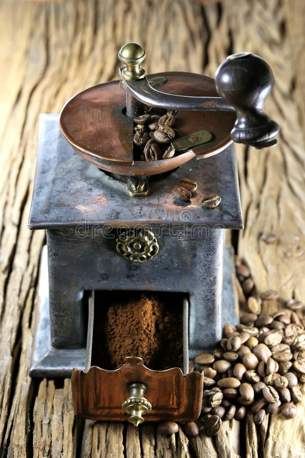 Coffee grinder. Vintage coffee grinder with manufacture roasted Indonesian Arabica coffee beans on rustic wooden background stock photo
