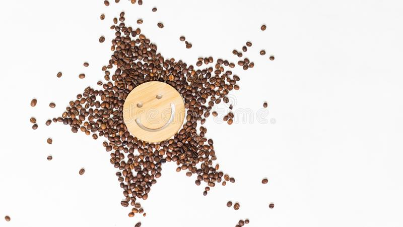 Coffee is a healthy, mood-enhancing drink. Star or sun from roasted coffee beans with a smile in the middle on a white. Background royalty free stock photography