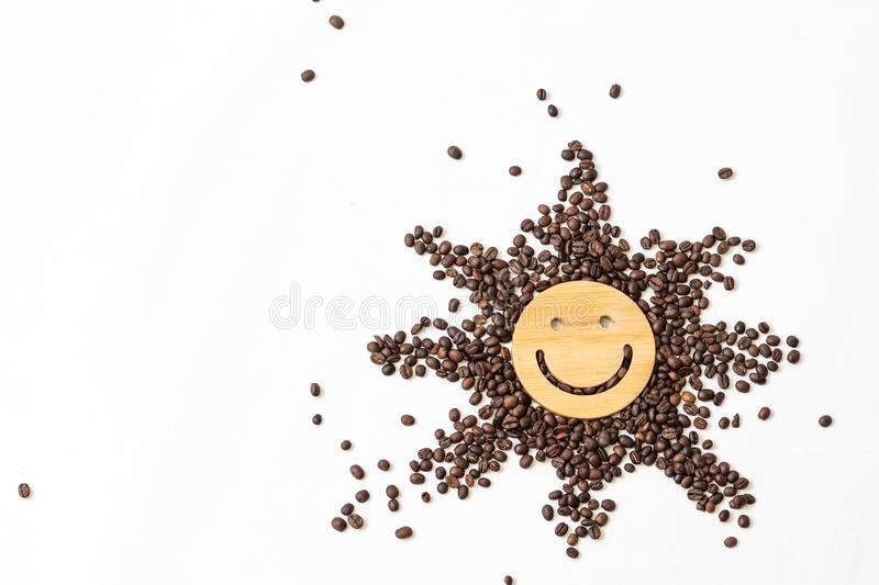 Coffee is a healthy, mood-enhancing drink. Star or sun from roasted coffee beans with a smile in the middle on a white. Background stock images