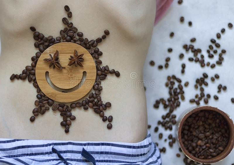 Coffee is a healthy, mood-enhancing drink. Star sun with a smile of coffee beans on the belly of a young girl. No face. Coffee is a healthy, mood-enhancing stock photo