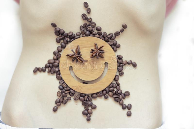 Coffee is a healthy, mood-enhancing drink. Star sun with a smile of coffee beans on the belly of a young girl. No face. Coffee is a healthy, mood-enhancing stock photography