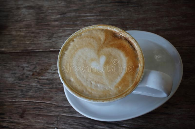 Coffee with heart in a white cup on wooden background royalty free stock images