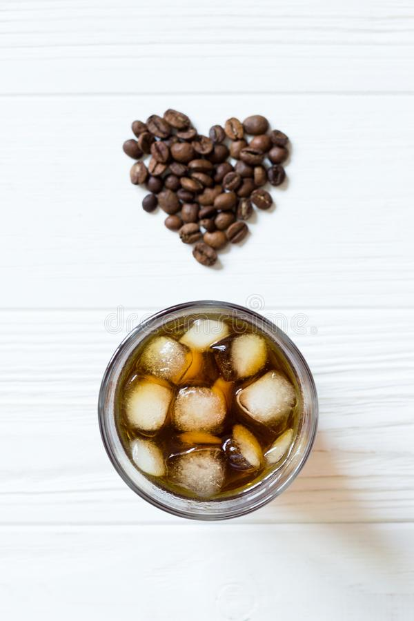 Coffee with ice and heart from coffee beans on white background. Top view royalty free stock photo