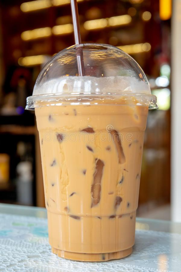 Coffee iced espresso with milk in plastic glass on wooden table at coffee shop or vintage restaurant. Closeup stock photo