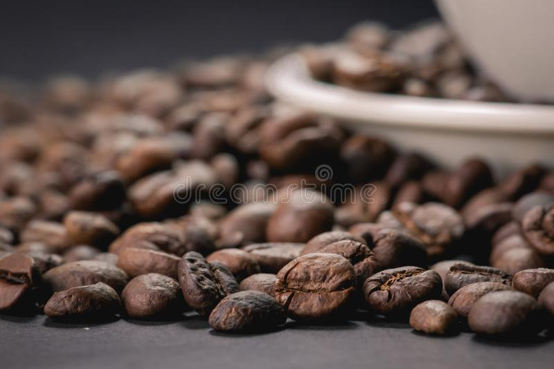 Coffee incup and coffee beans are the background. royalty free stock photography
