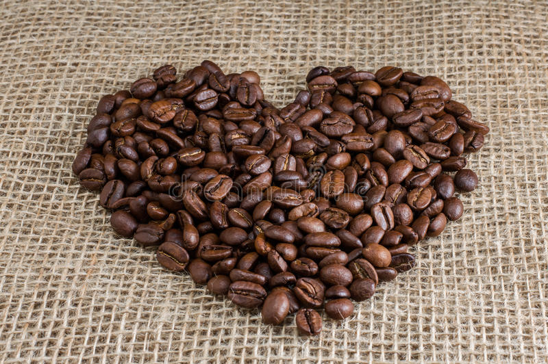 Coffee inlaid heart on fabric background royalty free stock photography