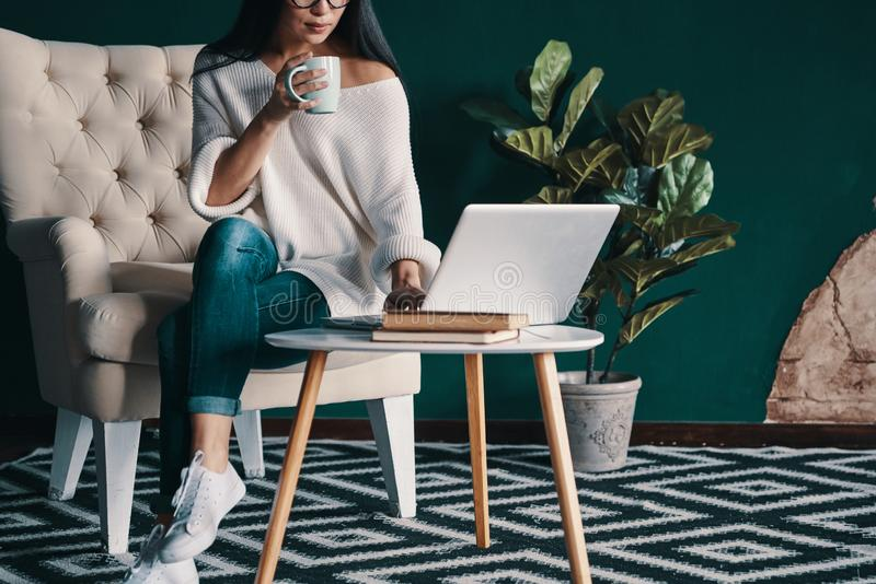 Coffee keeps her up. Close up of young woman using laptop and holding cup while sitting in the armchair stock image