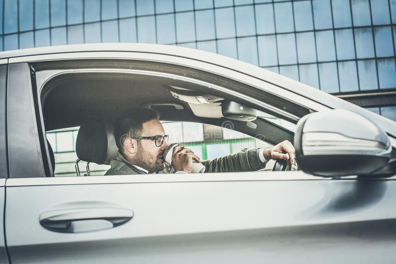 Coffee keeps him going. Business man driving car and drinking coffee. close up royalty free stock photo