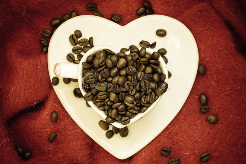Coffee klatsch java concept. Heart shaped cup filled with roasted coffee beans stock image