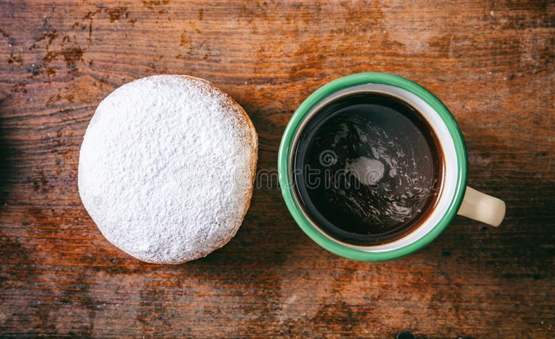 Coffee and krapfen with powder sugar, two, top view and isolated, wooden background. Breakfast concept. Coffee and krapfen with powder sugar, two, with top view stock image