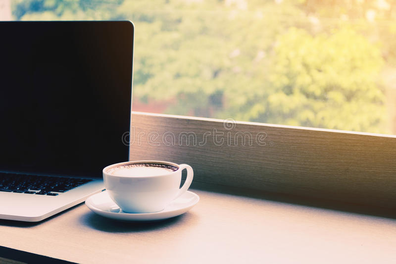 Coffee and laptop on desk bar in cafe with drink in morning. Coffee and laptop on desk bar in cafe with drink in morning stock photo