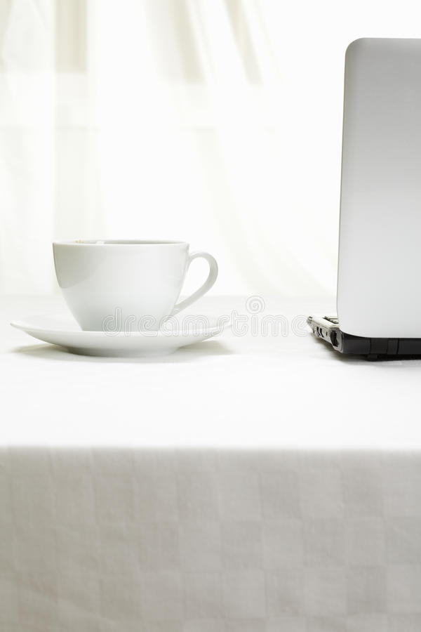 Coffee and laptop on white tablecloth