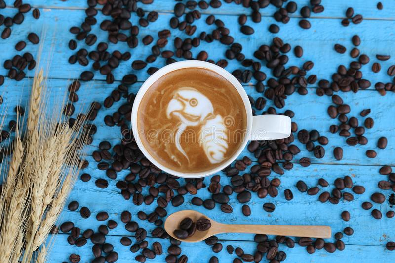 Coffee latte art with pattern the parrot in a cups on blue wooden background royalty free stock photos