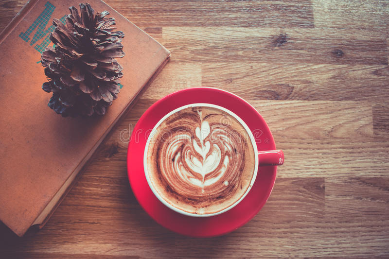 Coffee latte art in red cup with textbook on wood table. royalty free stock photos