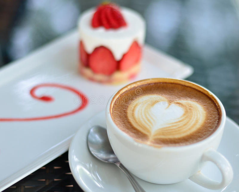 Coffee latte art and strawberry cake. Close up coffee latte art and strawberry cake stock photo