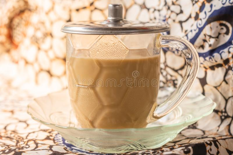 coffee latte with batik background royalty free stock photo