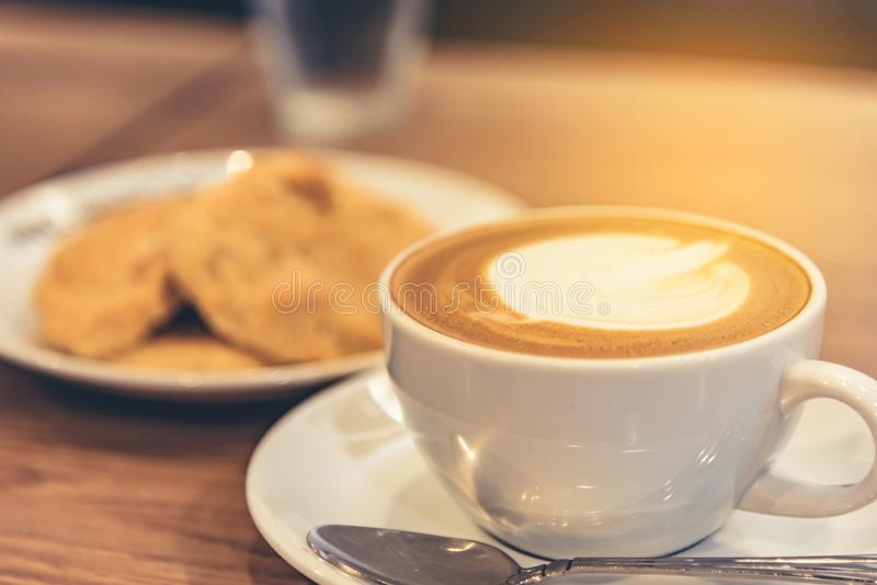 Coffee latte in cup with cookie on table stock photography