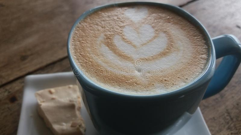Coffee latte in a cup with a piece of cake royalty free stock image