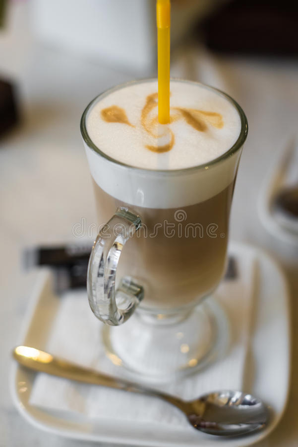 Coffee latte with a thick Crema. And yellow straw in a restaurant royalty free stock images