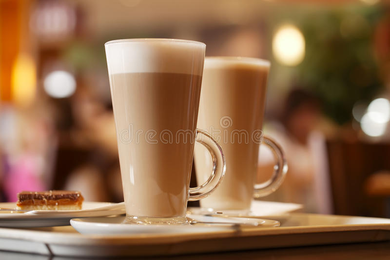 Coffee latte in two tall glasses inside cafe. Shallow dof stock image