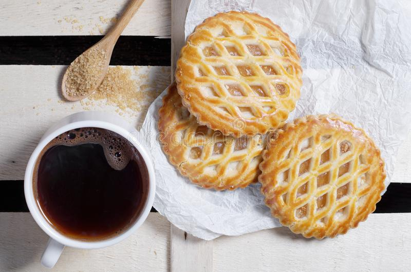 Coffee and lattice cakes with apple filling. Cup of coffee and lattice cakes with apple filling and brown sugar in wooden spoon, top view royalty free stock photo