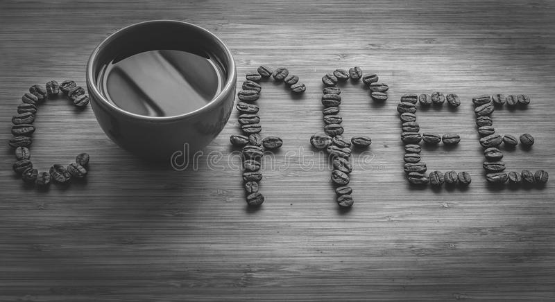 Coffee letters made of beans and cup on vintage boards. Black and white picture royalty free stock images