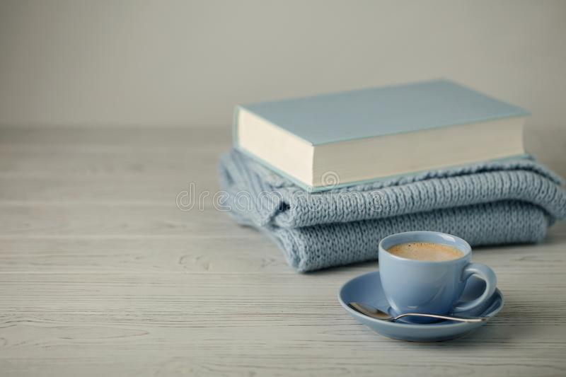Coffee in a light blue cup and book in blue binding with a knitted scarf on a wooden background. Selective focus royalty free stock photo