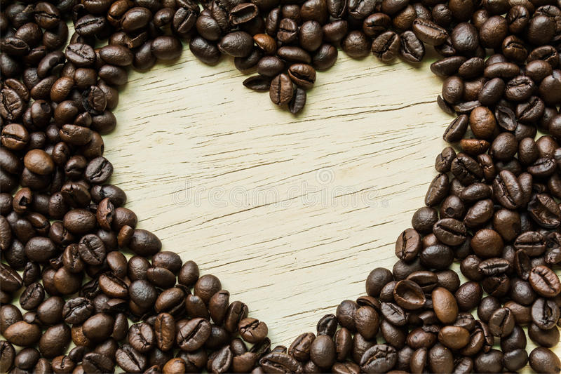 Coffee love, Coffee beans make a heart shape on a piece of wood. royalty free stock images
