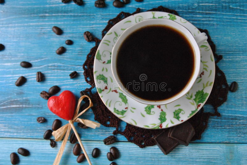 Coffee is love. Coffee still life: cup of coffee on a knitted napkin, coffee beans and red heart stock photography