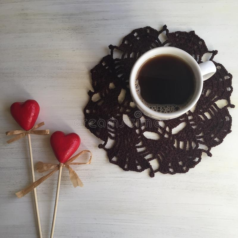 Coffee is love. Coffee still life: cup of coffee on a knitted napkin and red hearts royalty free stock photo