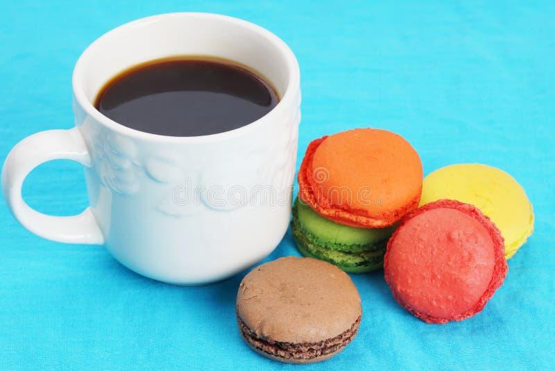 Coffee and macarons on blue