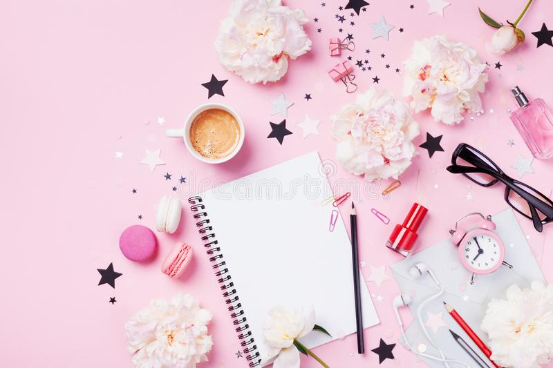 Coffee, macaroons, alarm clock, office supply, peony flowers and notebook on pink pastel table top view. Flat lay style. royalty free stock photos
